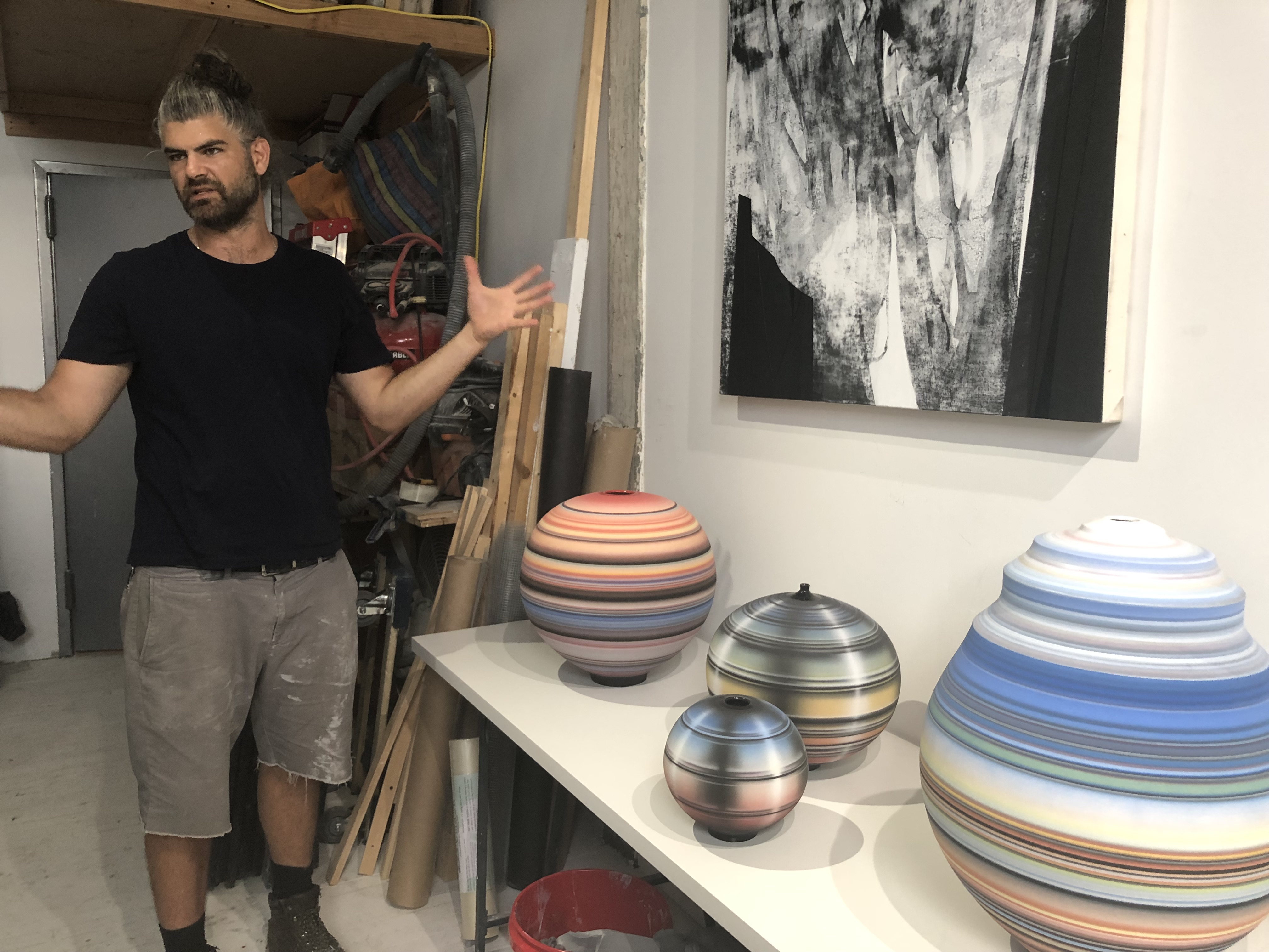 Artist Michael Dickey in his studio, showing ceramic sculptures and paintings