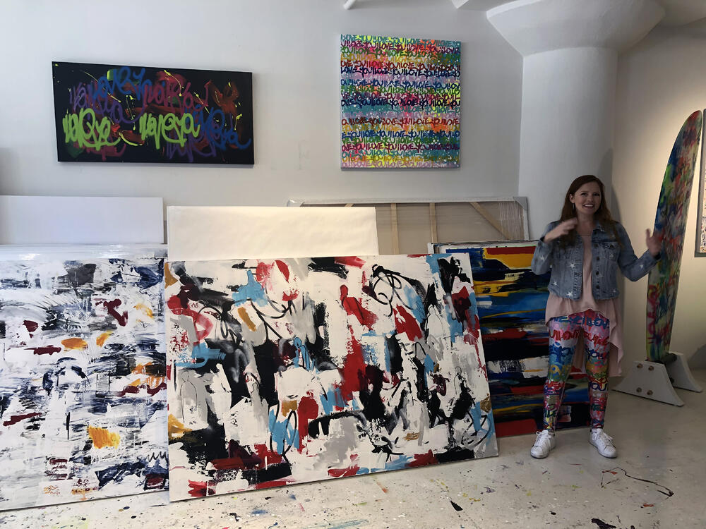 The artist, clad in custom leggings sporting her I Love You graffiti, walked us through her evolution from abstract expressionism to text-based art.